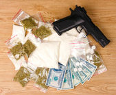 Cocaine and marihuana in packages, dollars and handgun on wooden background — Stock Photo