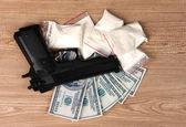 パッケージ、ドルおよび木製の背景に拳銃のコカイン — ストック写真