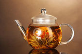 Glass teapot with exotic green tea on wooden table on brown background — Стоковое фото
