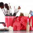 Red glass with brushes and makeup bag with cosmetics isolated on white — Stock Photo #8458407