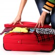 Stock Photo: Girl tries to close suitcase isolated on white