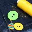 Stock Photo: Rhomb-shaped patch on jeans with threads and buttons closeup