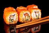Delicious sushi and chopsticks on black background — Stock Photo