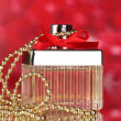Perfume bottle with red bow on red background — Stock Photo