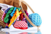 Bright threads for needlework and fabric in a wicker basket — Stock Photo