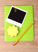 Photo paper and green notebook on wooden background — Stock Photo