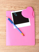 Photo paper and pink notebook on wooden background — Stock Photo