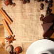 Coffee cup and beans, cinnamon sticks, nuts and chocolate on sacking on woo - Stockfoto