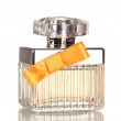 Perfume bottle with orange bow isolated on white — Stock Photo