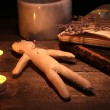 Royalty-Free Stock Photo: Voodoo doll boy on a wooden table in the candlelight