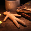 Stock Photo: Voodoo doll boy on a wooden table in the candlelight