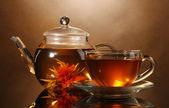 Cam çaydanlık ve bardak kahverengi backgro üzerinde ahşap masa üstünde egzotik yeşil çay ile — Stok fotoğraf