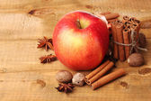 Cinnamon sticks,red apple, nutmeg,and anise on wooden table — Stock Photo