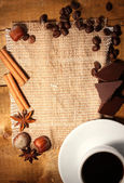 Coffee cup and beans, cinnamon sticks, nuts and chocolate on sacking on woo — Stock Photo