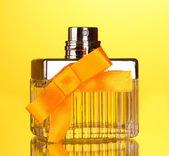 Perfume bottle with orange bow on yellow background — Stock Photo