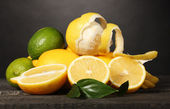 Ripe lemons and limes with leaves on wooden table on grey background — Stock Photo