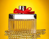 Perfume bottle with red bow on yellow background — Stock Photo