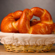 Baked bread in basket on wooden table on grey background - Foto de Stock