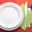 White empty plate with fork, spoon and knife on a red tablecloth — Stock Photo #8520124
