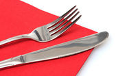 Fork and knife in a red cloth isolated on white — Stock Photo