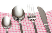 Fork, spoon and knife in a plaid cloth with a bow isolated on white — Stock Photo