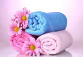 Towels and beautiful flowers on pink background — Stock Photo