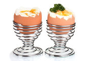 Boiled eggs in metal stands and parsley isolated on white — Stock Photo
