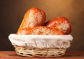 Baked bread in basket on wooden table on brown background — Stock Photo