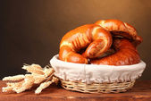 Baked bread in basket on wooden table on brown background — Стоковое фото