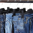 Jeans on hangers isolated on white - Stockfoto