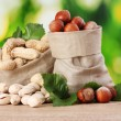 Many nuts in bags on green background — Foto Stock