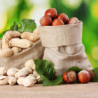 Many nuts in bags on green background — Stockfoto