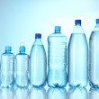 Group plastic bottles of water on blue background — Stock Photo