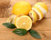 Ripe lemons with leaves on wooden table — Stock Photo