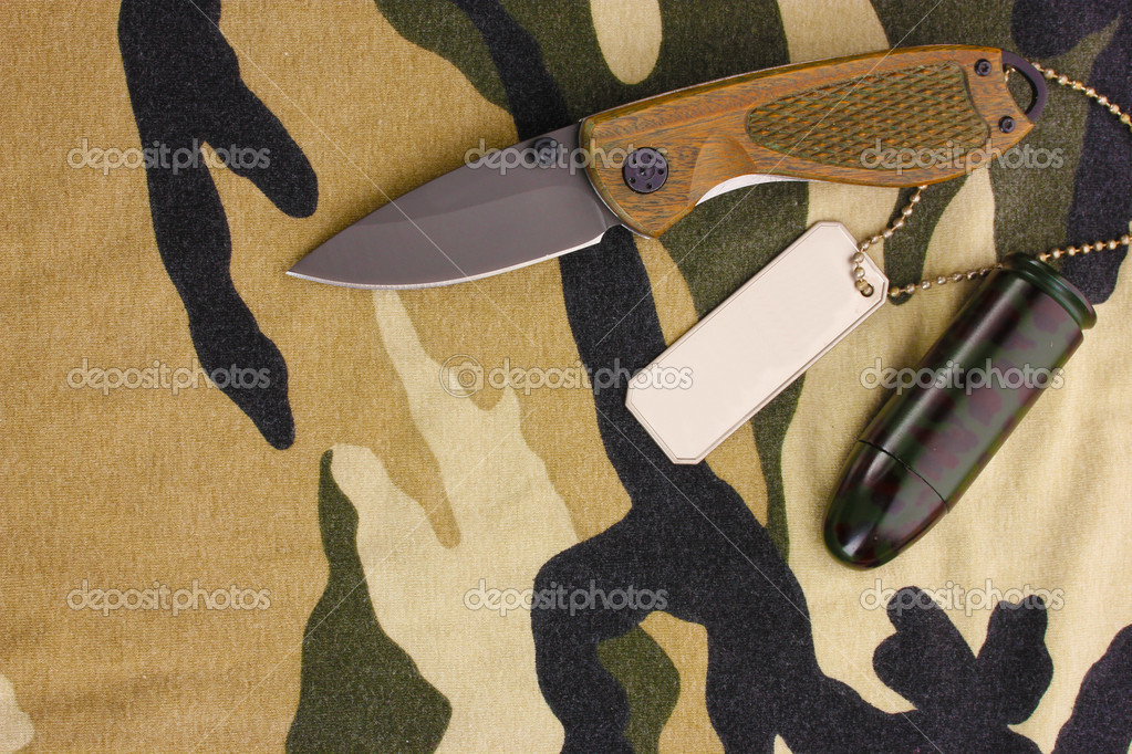 Army badges and knife on camouflage background — Stock Photo #8564656