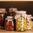 Delicious marinated mushrooms in the glass jars on wooden shelf - Stock Photo