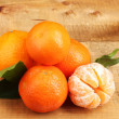 Tangerines with leaves on wooden table — Stock Photo