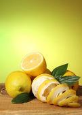 Mogna citroner med blad på träbord på grön bakgrund — Stockfoto