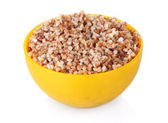 Boiled buckwheat in a yellow bowl isolated on white — Stock Photo