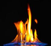 Flaming vodka on black background — Stock Photo
