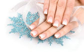 Hands with beautiful winter design, snowflakes and ribbon solated on white — Stock Photo