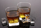 Two glasses of scotch whiskey and ice on grey table — Stock Photo