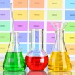 Three flasks with color liquid on color samples background — Foto Stock