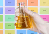Flask with yellow liquid in hand on color samples background — Stock Photo