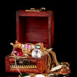 Wooden chest full of gold jewelry on black background — Stock Photo #8617539