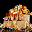 Various gold jewellery and gifts on black background — Stock Photo