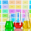 Three flasks with color liquid on color samples background - Stock Photo
