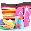 Bright striped beach bag and beach items isolated on white — Stock Photo