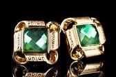 美丽的金耳环,用黑色的背景上的绿宝石 — 图库照片