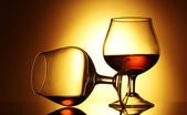 Two glasses of cognac on yellow background — Stock Photo